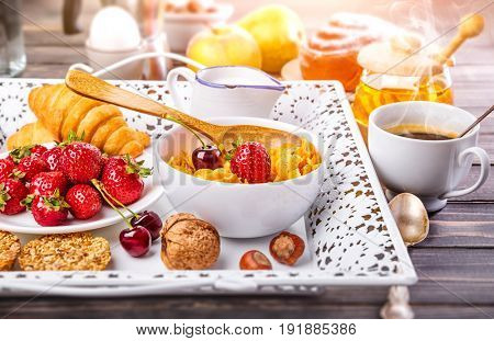 Breakfast with cornflakes berry honey and croissant on wooden board white tray.