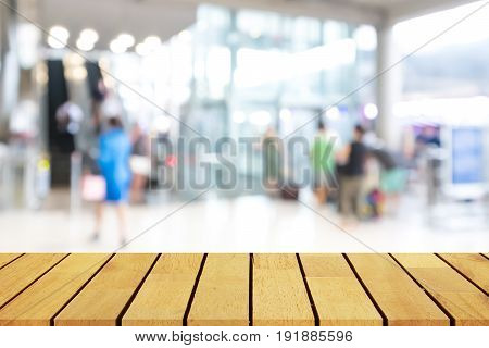 Prespective empty wooden table over blurred shopping mall background for product display montage or design layout.