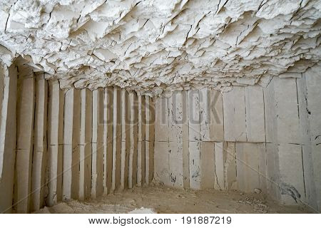 Grungy white cream limestone wall cave with scratches texture and light falloff from miner mining