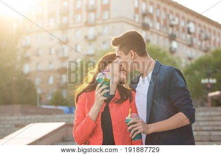 Teenagers drink fruit fresh from glasses. A humble first kiss. Couple in love. Romance of first love.