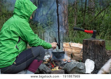 Woman traveler cooking food in kettle on fire in forest.