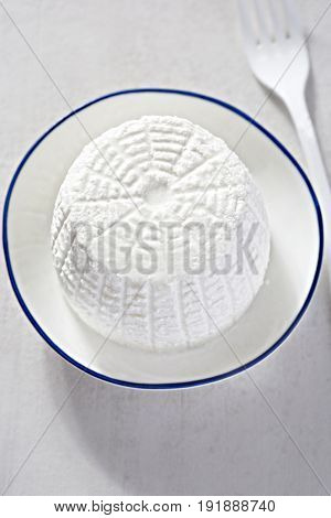Fresh ricotta cheese on white plate and white table