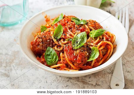 Meatballs in tomato sauce with spaghetti and fresh basil