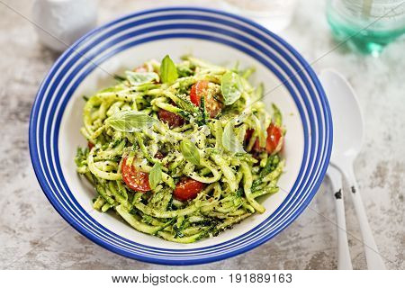 Spiralled courgette spaghetti with green pesto and cherry tomatoes.
