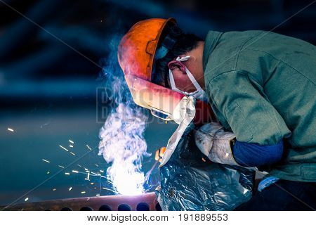 Worker doing electric welding in factory,manufacturing industry concepts.
