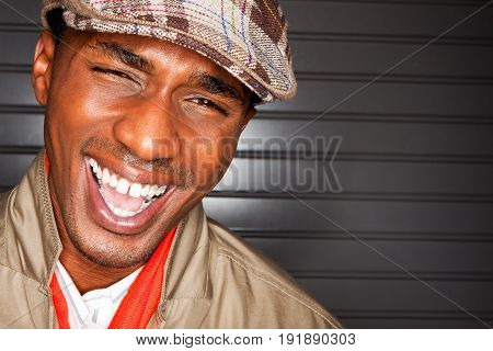 Happy fashionable young man laughing isolated on a grey wall.