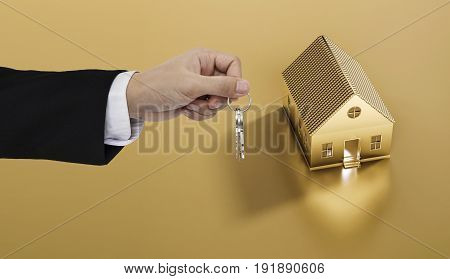 Hand holding keys with golden land and house background, real estate and property concepts