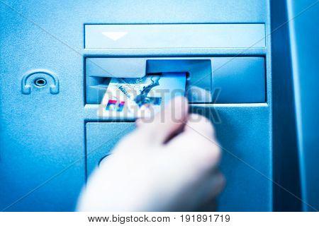 Woman hand using cash machine-ATM,close up view.