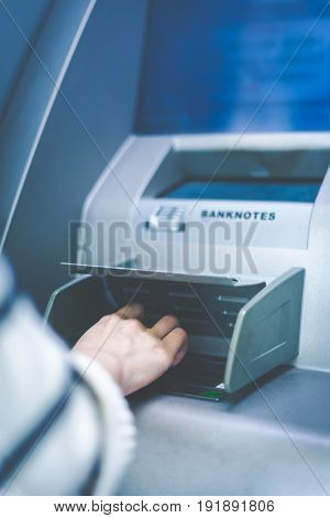 Woman hand touching cash machine-ATM,close up view.