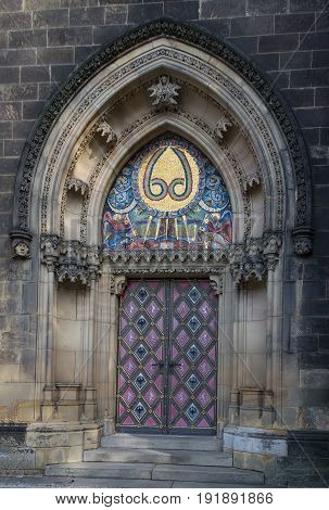 Front door with stone mosaic of basilica of St Peter and St Paul in Vysehrad in Prague.