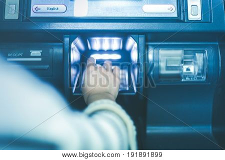 Woman hand using cash machine-ATM,close up view.