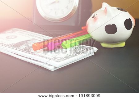 Piles of US dollar banknotes and small piggy bank on black floor for money saving concept
