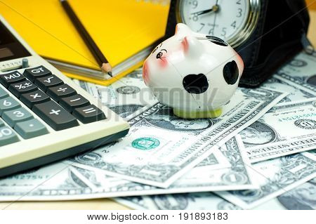 Small piggy bank and financial calculator on Piles of US dollar banknote. For money saving concept