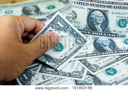 Hand picking US dollar banknote from stack of banknotes on the floor