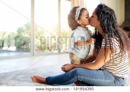 Black Mother Kissing Child Sitting On Floor