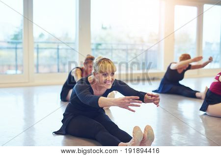 Fit smiling ballerinas sitting on floor and stretching while doing gymnastics in ballet class.