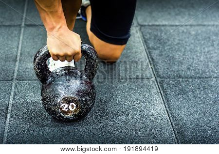 Kettle bell workout. Woman holding kettle bell on the gym floor.