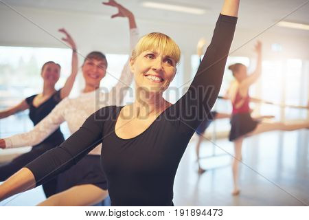 Cheerful smiling adult ballerina stretching with hand up performing a dance in ballet class.