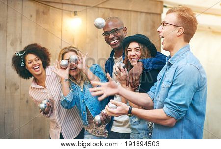 Excited Man Throwing Up Petanque Ball In Front Of Friends