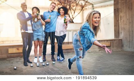 Young Woman Throwing Petanque Ball Playing With Friends