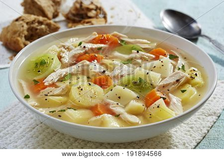 Wholesome chicken soup stew with fresh roll