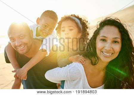 Cheerful smiling African-American man and woman carrying and holding on back their children on sandy beach.