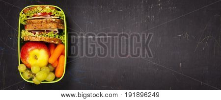 Green school lunch box with sandwich, apple, grape and carrot close up on black chalkboard background. Healthy eating habits concept. Flat lay composition (from above, top view). Space for text