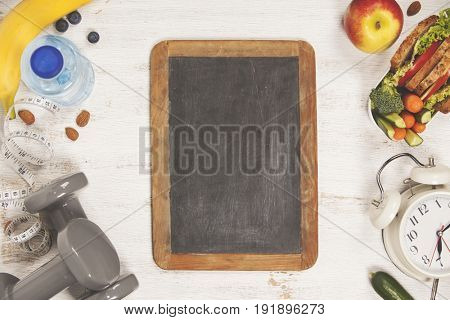 Health & Fitness Food in lunch box, measuring tape, dumbbells and alarm clock on wooden board.