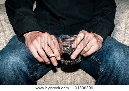 Alcohol and cigarettes. Man holding a glass of whiskey and smoking a cigarette.