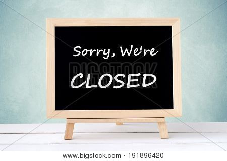 Sorry we're close on blackboard over green wall background business hours sign