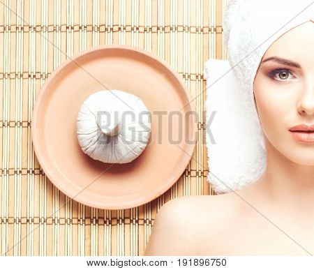 Beautiful girl getting health care treatment in spa salon. Woman over bamboo mat. Healing, spa and oriental therapy concept.