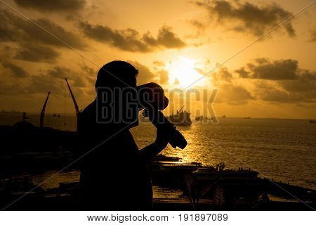 Silhouette man take a photo on a port in MaleMaldives