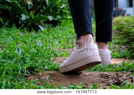 Girl with sneakers walking in park background spring summer fashion lifestyle concept