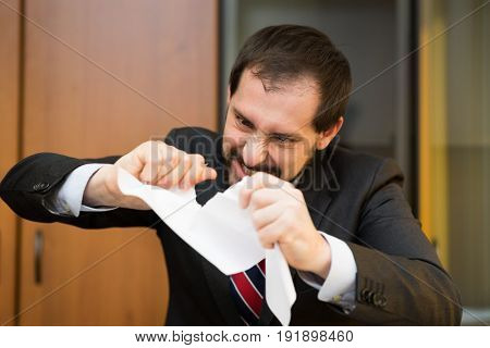 Angry businessman tearing apart a document