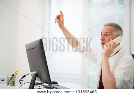 Businessman talking on the phone and raising his arm while using his computer