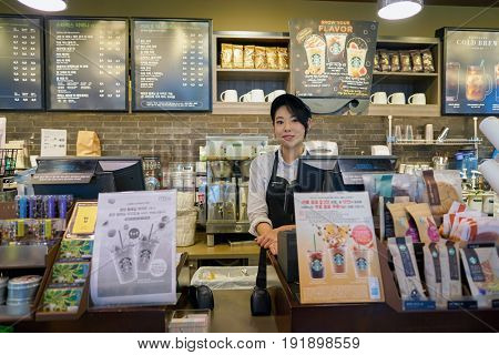 SEOUL, SOUTH KOREA - CIRCA MAY, 2017: indoor portrait of a worker at Starbucks. Starbucks Corporation is an American coffee company and coffeehouse chain.