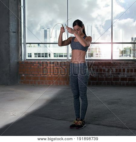 Woman athlete jumping with skipping rope in gym. Fitness concept
