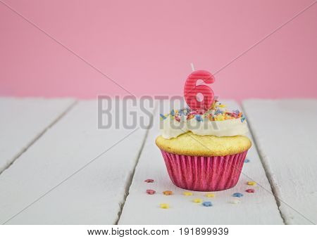 Happy birthday cup cake with pink number 6 candle on white wood table for little girl