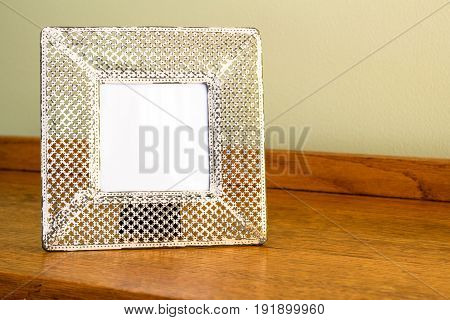 Photo frame - Wide cream coloured metal punched delicate frame with white blank space for image or text standing on oak wood table indoors - background