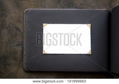 Photo frame - real old photo with white blank space for copy photo with gold coloured photo holder corners onto black vintage album paper page - top view background with space for text