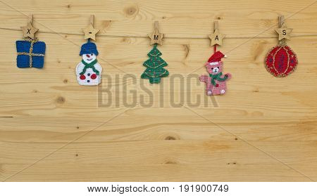 Several crocheted christmas hangers on a cord on wood and text x-mas, background