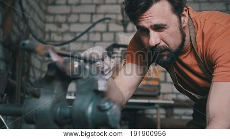 Portrait of a blacksmith who checks the symmetry of the knife blanks