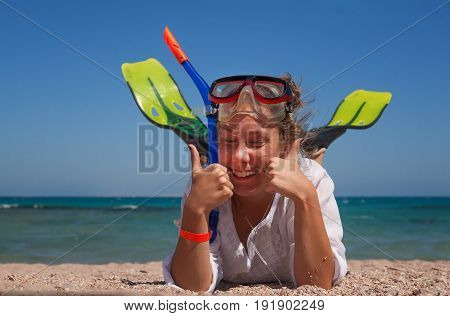 young woman in a mask and fins for scuba diving with his eyes closed lying on the sand laughing and showing thumbs up ok. The concept of a hilarious and excellent holiday on the beach.