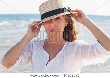 A young woman in a straw hat fervently laughing against the background of the sea a large portrait. The concept of a young and healthy lifestyle.