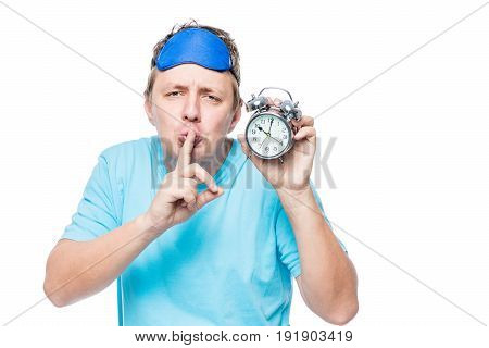 Emotional Sleepy Man With An Alarm Clock Shows A Gesture Quieter On A White Background
