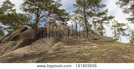The top of the hill on the coast of lake Baikal, topped with huge boulders and young pine trees.