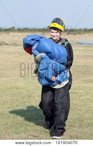 Attractive Female Sky Diver Posing With Bright Blue Parachute And Yellow Helmet After Safe Landing.