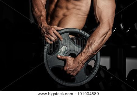man in gym. Muscular bodybuilder guy doing exercises with barbell. Strong person with Tense strong male hand with veins barbell