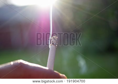 Smoke rising from burning cigarette to sun / heaven.