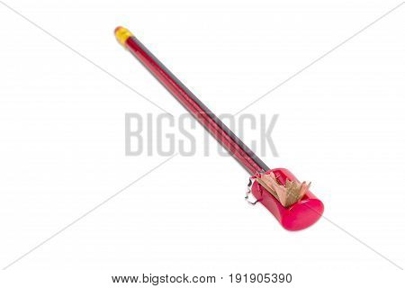 Manual prism pencil sharpener in red plastic housing and the pencil with long shavings during sharpening closeup on a light background